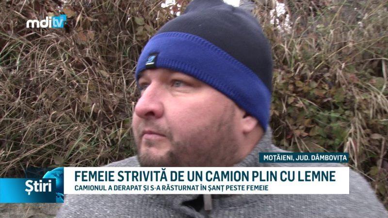 FEMEIE STRIVITĂ DE UN CAMION PLIN CU LEMNE